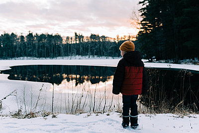 Little boy by a half frozen lake during sunset. - p1166m2157334 by Cavan Images