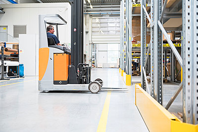 Worker on forklift in high rack warehouse - p300m2188425 by Daniel Ingold