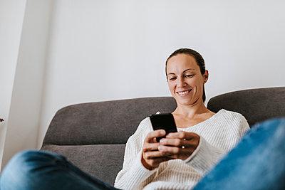 Smiling woman using phone on sofa at home - p300m2240174 by David Molina Grande