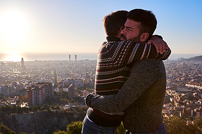 Gay boyfriends embracing while standing against cityscape during sunrise, Bunkers del Carmel, Barcelona, Spain - p300m2256692 by Veam