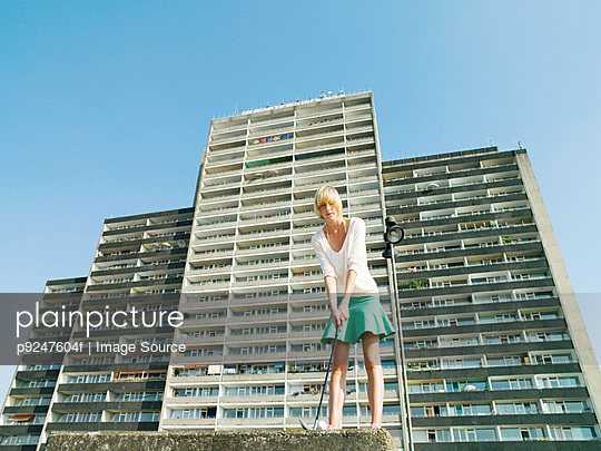 Woman playing golf by apartment block - p9247604f by Image Source