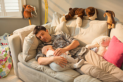 Exhausted father and baby son sleeping on sofa - p1023m1446509 by Tom Merton