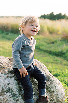 Little toddler boy looking proud whilst sitting on a big rock. - p1166m2151880 by Cavan Images