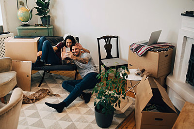 Smiling couple video calling through mobile phone while sitting in living room during relocation - p426m1542771 by Maskot