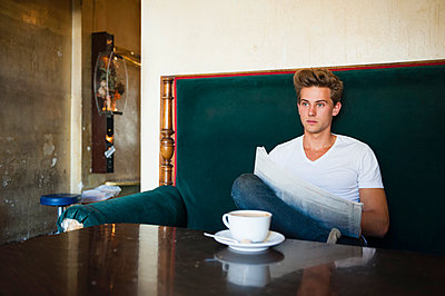 Young man sitting at table in cafe reading newspaper - p429m983380f by Daniel Ingold