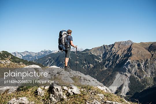 Junger Wanderer genießt Ausblick in Berge  - p1142m2056570 von Runar Lind