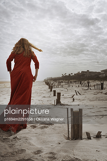 Young red-haired woman in a long red dress running away on the hurricane-damaged beach  - p1694m2291656 by Oksana Wagner