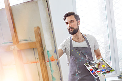 Male artist with palette painting at easel in art studio - p1023m1506505 by Rafal Rodzoch