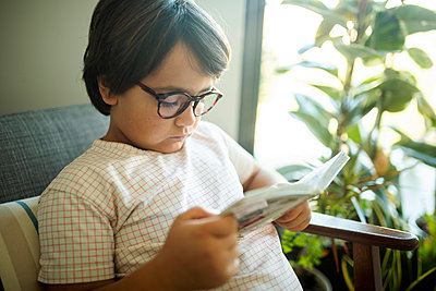 Portrait of serious boy with glasses reading book at home - p300m2167151 by Valentina Barreto