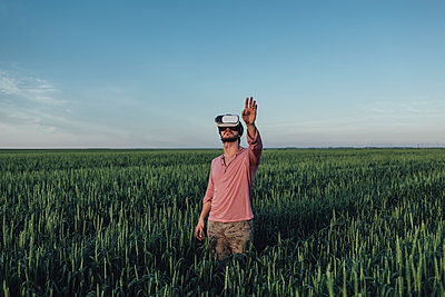 Man using virtual reality headset while gesturing in field against blue sky - p301m1406594 by Vasily Pindyurin