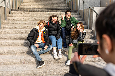 Cropped image of teenage girl photographing multi-ethnic friends sitting on steps in city - p426m1588368 by Maskot