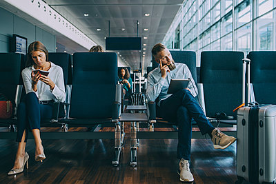 Thoughtful businessman looking away while sitting by female colleague at waiting area in airport - p426m2074532 by Maskot