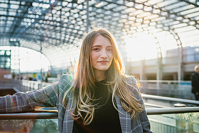 Young woman with long blond hair in sunlit train station, portrait, Turin, Piemonte, Italy - p429m2097862 by Francesco Buttitta