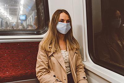 Junge Frau mit Mundschutz unterwegs mit der U-Bahn - p432m2184844 von mia takahara