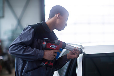 Workman fixing car windshield in workshop - p924m2165042 by Sigrid Gombert