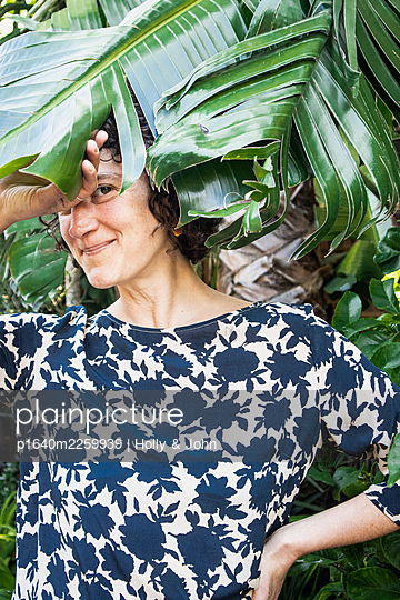 Woman under a palm tree, portrait - p1640m2259939 by Holly & John
