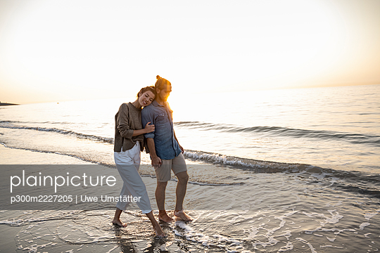 Young couple walking on shore at beach during sunset - p300m2227205 by Uwe Umstätter