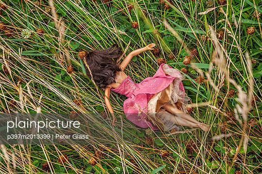 Kinderpuppe liegt im hohem Gras - p397m2013399 von Peter Glass
