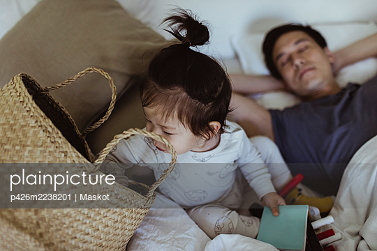 Male toddler peeking in basket while father sleeping on bed at home - p426m2238201 by Maskot