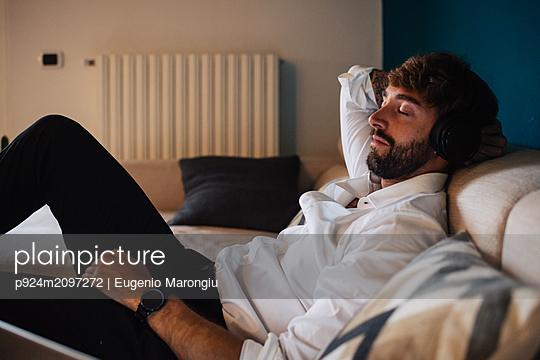 Mid adult man reclining on sofa listening to headphones with eyes closed - p924m2097272 by Eugenio Marongiu