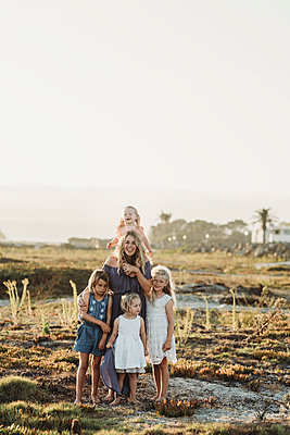 Lifestyle portrait of mother with young girls smiling at beach sunset - p1166m2165892 by Cavan Images