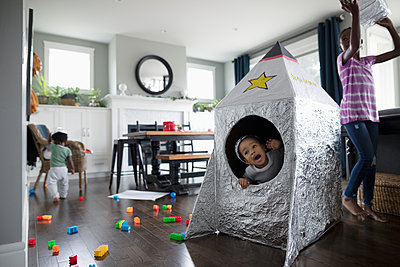 Playful brother and sisters playing with toy spaceship in living room - p1192m2046982 by Hero Images