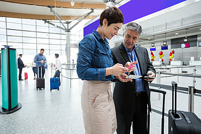 Business people holding boarding pass and using mobile phone - p1315m1199585 by Wavebreak