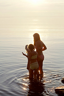 Girls wading in lake at sunset - p312m695567 by Ulf Huett Nilsson