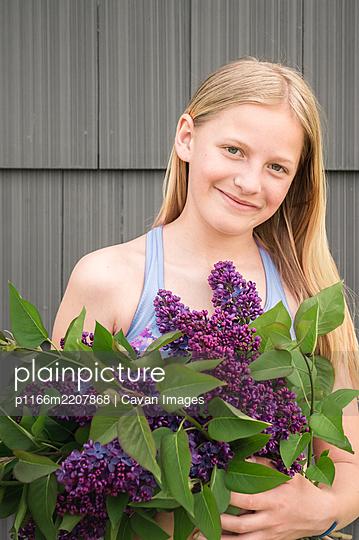 Tween Girl Holding Bunch of Purple Lilac Flowers and Smiling - p1166m2207868 by Cavan Images