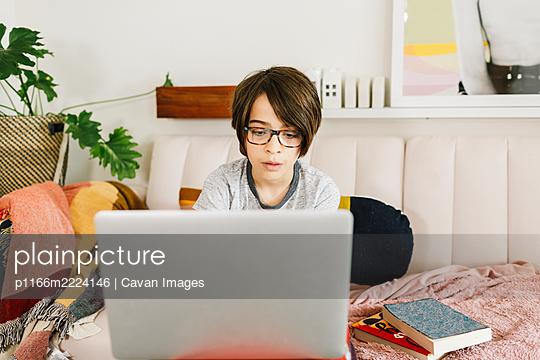 Boy havig a remote meeting  online on living room - p1166m2224146 by Cavan Images