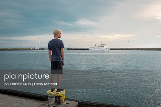 Poland, Gdansk Bay, teenage boy standing on quay looking at distance - p300m1587498 von Hans Mitterer