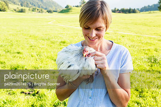 Woman carrying rooster in countryside, Sonthofen, Bayern, Germany - p429m2074975 by Brigitte Sporrer