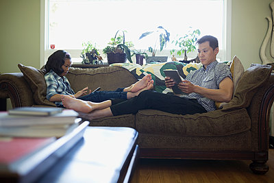 Barefoot father and daughter using digital tablets on living room sofa - p1192m1157989 by Hero Images