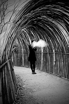 Woman in bamboo tunnel with cloud - p1521m2228360 by Charlotte Zobel