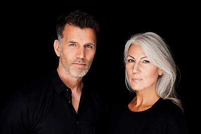 Portrait of mature man and mature woman wearing black clothes in front of black background - p300m1081423f by Chris Adams