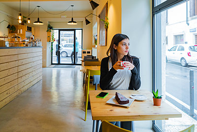 Young woman sitting in a cafe looking out of window - p300m2139929 by Giorgio Fochesato