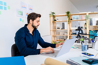 Male entrepreneur looking at document while using laptop in office - p300m2251950 by Giorgio Fochesato