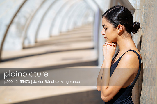 Young woman wearing black swimsuit leaning against a wall in an archway - p300m2155470 by Javier Sánchez Mingorance