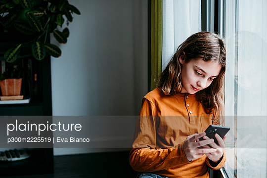 Girl using mobile phone while leaning on window at home - p300m2225519 by Eva Blanco