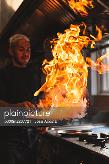 Chef with flame on frying pan in kitchen - p300m2287721 by Josu Acosta