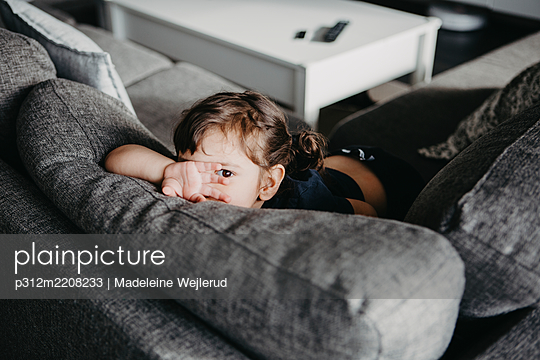 Girl on sofa looking at camera - p312m2208233 by Madeleine Wejlerud