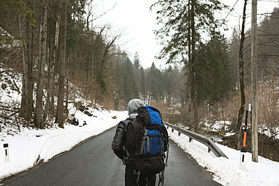Rear view of male hiker with backpack walking on road in forest during winter - p1166m2024601 by Cavan Images