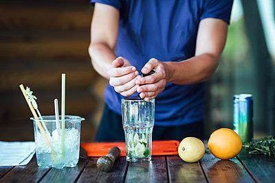 Barman prepares fruit alcohol cocktail based on lime, mint, oran - p1166m2094693 by Cavan Images