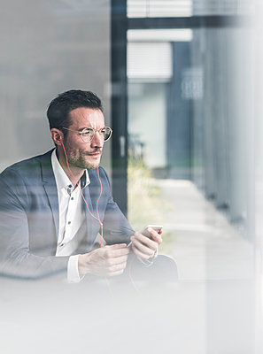 Businessman talking on the phone, using earphones - p300m2059512 von Uwe Umstätter