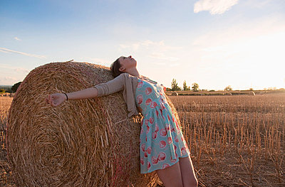 Girl leaning on haystack in field - p42916832f by Simon Potter