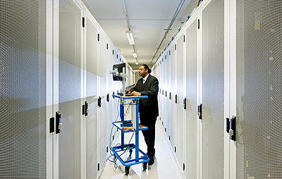 Businessman using computer with servers - p429m665596f by Mischa Keijser