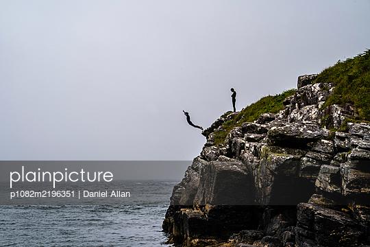 Teenager springen von einer Klippe ins Meer - p1082m2196351 von Daniel Allan