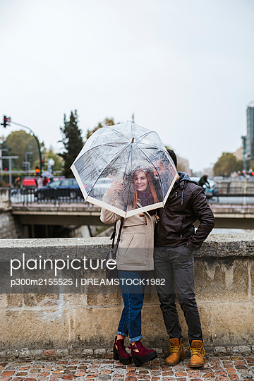 Couple in love with transparent umbrella in autumn - p300m2155525 by DREAMSTOCK1982