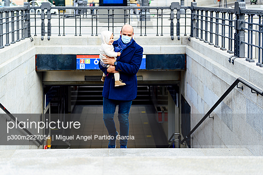Man with face mask carrying baby while walking on staircase in city - p300m2227054 by Miguel Angel Partido Garcia