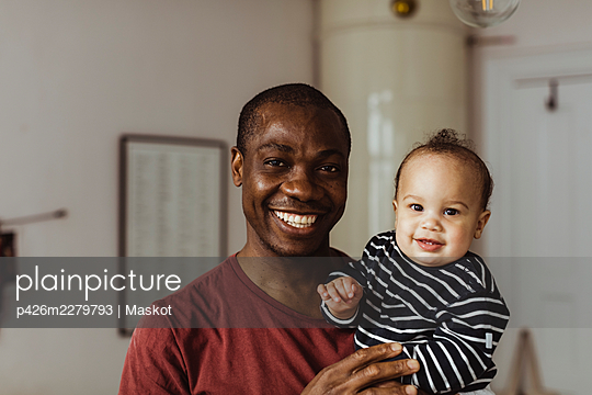 Portrait of smiling father and toddler son at home - p426m2279793 by Maskot
